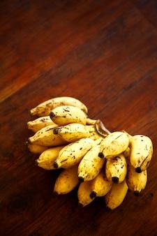 Связка маленьких спелых бананов на столе