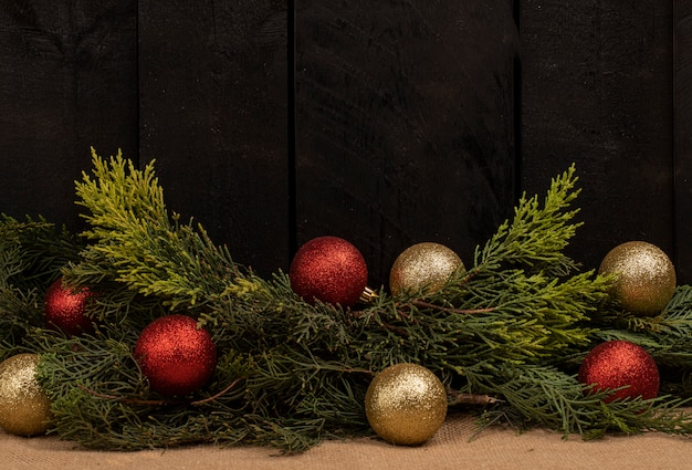 Oの木の枝と黒い木製の背景に輝くボールの束
