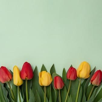 緑の背景にピンクと黄色のチューリップの束と、お祝いのイベントや会議へのテキスト招待用のコピースペース。バレンタインまたは母の日のコンセプト。