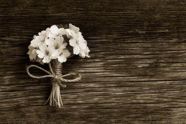 割れ目で古い木の板にひもで結ばれたサクラソウの束