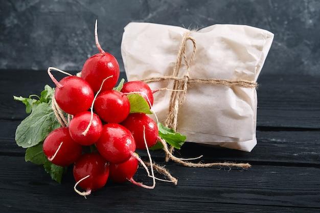 Пучок редиса на темном фоне, свежие овощи из сада, место для текста.