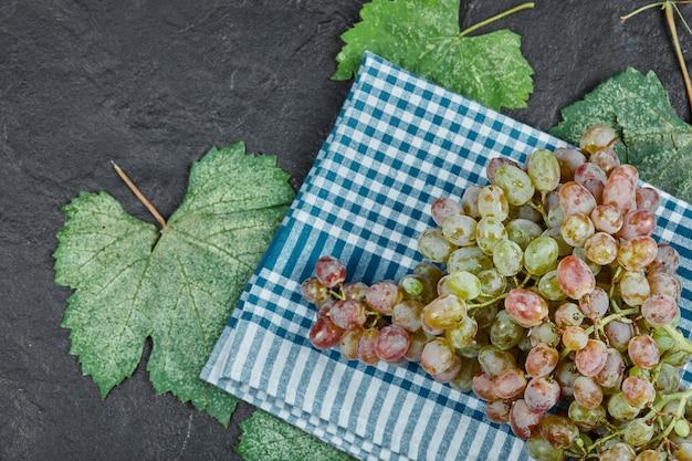 잎과 어두운 배경에 파란색 식탁보와 붉은 포도의 무리. 고품질 사진