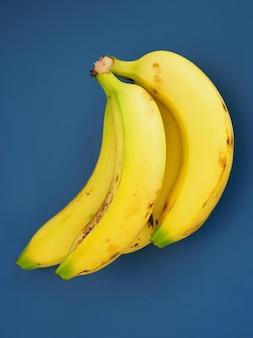 青色の背景にドミニカ共和国からの熟した黄色のバナナの束。
