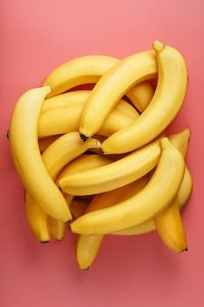 ピンクの背景に熟した黄色のバナナの束。上からの眺め。ミニマルなコンセプト。フリースペース