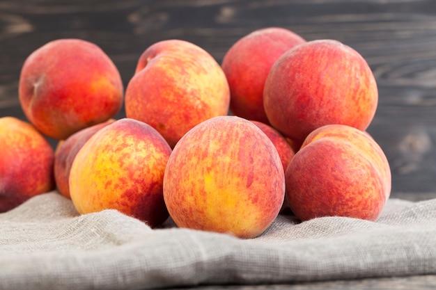 Пучок спелых желто-оранжевых плодов персика на льняной салфетке, крупным планом
