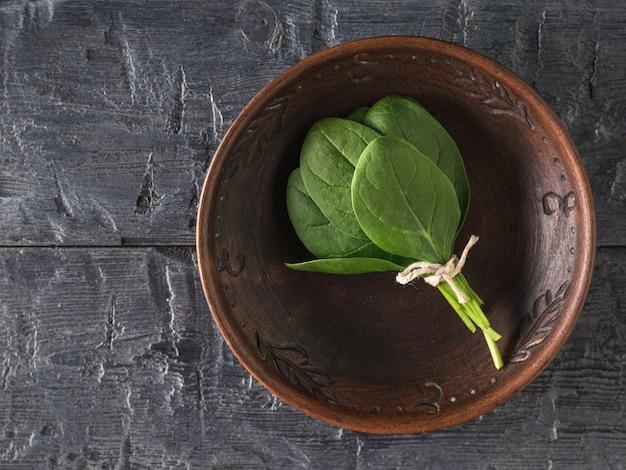 검은 나무 탁자 위의 점토 그릇에 시금치 잎 한 뭉치가 있습니다. 건강을 위한 음식. 채식주의 자 음식.