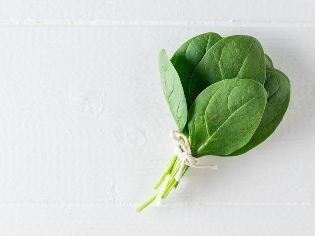 흰색 나무 테이블에 시금치 한 뭉치 잎. 건강을 위한 음식. 채식주의 자 음식. 정상에서 본 모습.