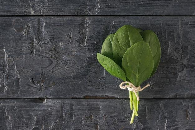 검은 소박한 테이블에 밧줄로 묶인 시금치 잎의 무리. 건강을 위한 음식. 채식주의 자 음식.