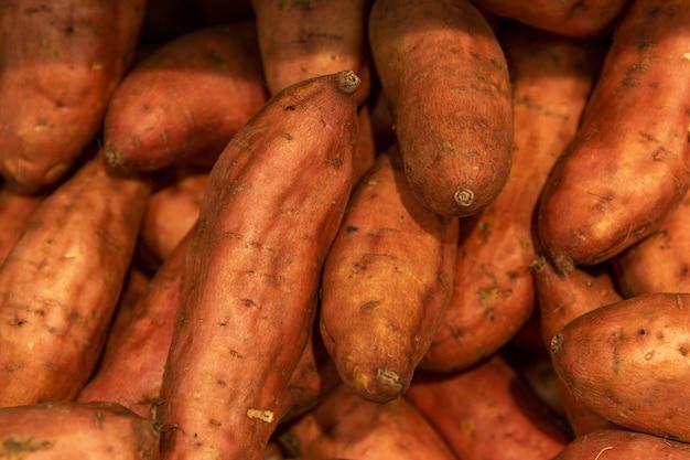 店内にたくさんのサツマイモ。ビタミンと健康食品。バックグラウンド。