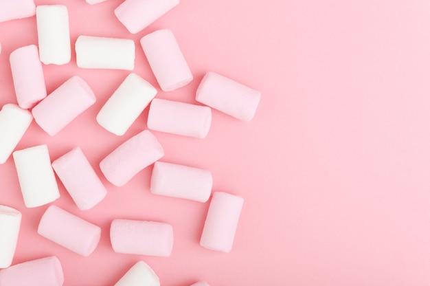 パステルカラーの明るい背景に白とピンクのマシュマロの束。