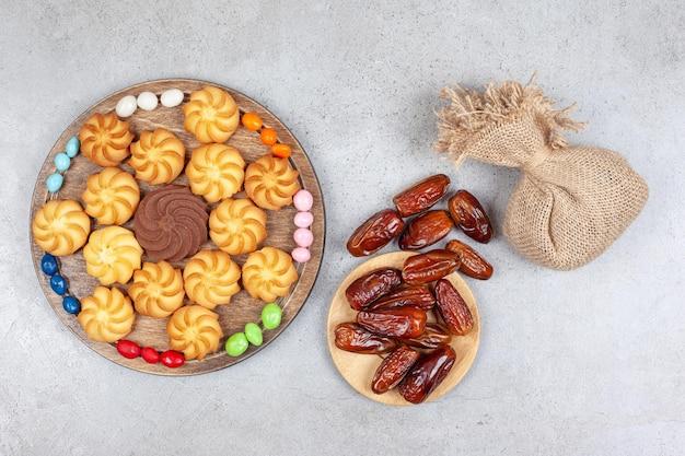 Пачка фиников и мешок с деревянной доской декоративно расставленных конфет и печенья на мраморном фоне. фото высокого качества
