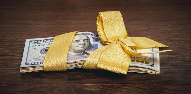Пачка долларов перевязана лентой с бантом, деньги в подарок