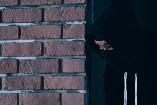 Грабитель в темном и кожаном плаще разбивает окно дома.
