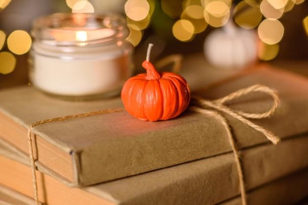 Горящая свеча на деревянном столе перед книгой в полумачте. обучение. изучение библии