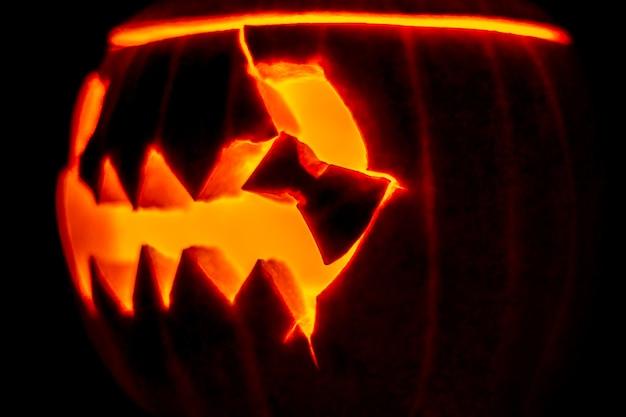 Горящая голова, вырезанная из тыквы со зловещей улыбкой к празднику хэллоуина. обугленный фонарь джека со свечой внутри в темноте