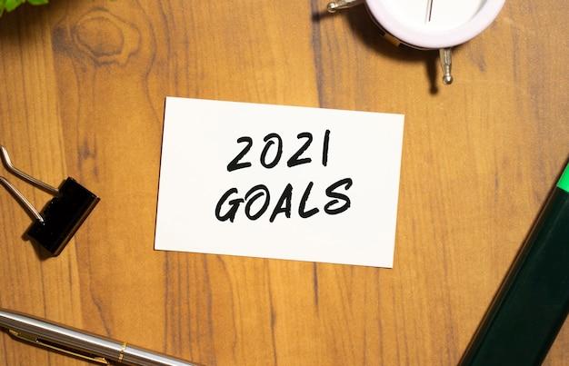Визитная карточка с текстом цели 2021 лежит на деревянном офисном столе среди канцелярских товаров.