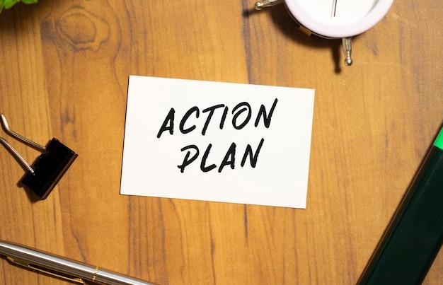 Визитная карточка с текстом план действий лежит на деревянном офисном столе среди канцелярских товаров.