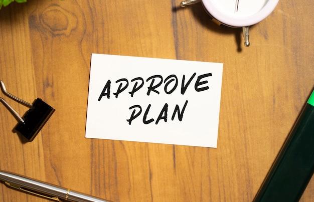Approve planというテキストの名刺は、事務用品の中の木製のオフィステーブルにあります。ビジネスコンセプト。