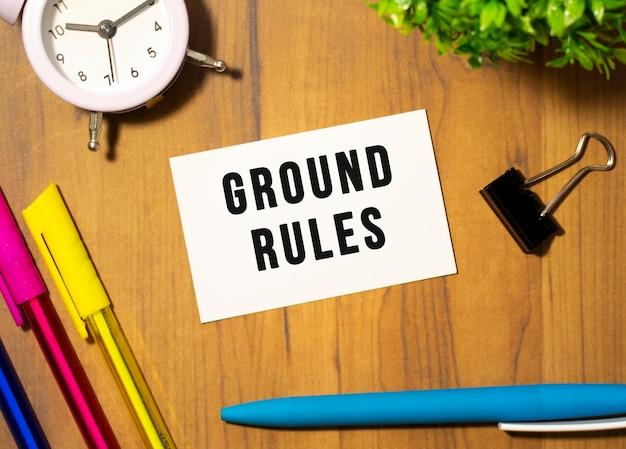 Ground rulesというテキストの名刺は、事務用品の中の木製のオフィステーブルにあります。