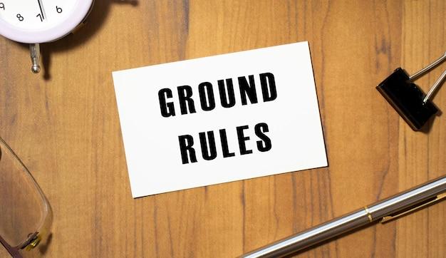 텍스트 ground rules가있는 명함이 나무 사무실 테이블에 놓여 있습니다.