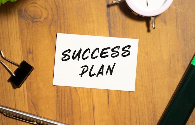 성공 계획이라는 텍스트가있는 명함이 사무용품 중 나무 사무실 테이블에 놓여 있습니다.