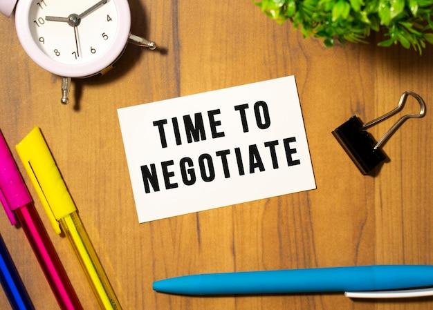 Визитная карточка с текстом «время переговорать» лежит на деревянном офисном столе среди канцелярских товаров. бизнес-концепция.