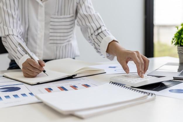 비즈니스 재무 여성이 비즈니스 파트너와의 회의를 위해 재무 부서에서 준비한 회사 재무 문서를 검토하고 있습니다. 재무 숫자의 정확성을 검증하는 개념.