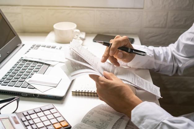 Ручка удерживания бизнесмена пока смотрящ счеты в его рабочем месте. бизнес-концепция