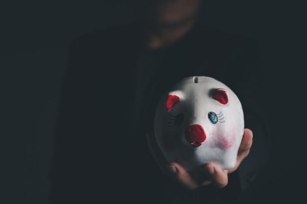 흰색 돼지 저금통을 들고 있는 사업가, 개별 텍스트를 위한 복사 공간이 있는 클로즈업 샷, 절약 및 투자 개념