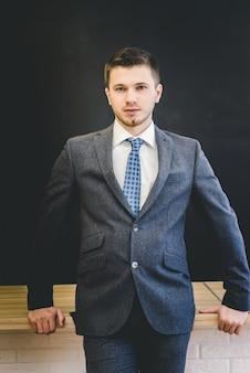 넥타이가 달린 재킷을 입은 사업가가 나무 테이블 옆에 서서 카메라를 바라보고 있다