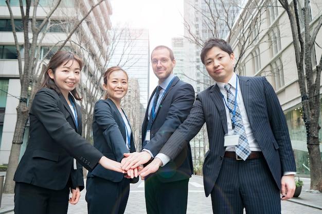 ビジネス地区の路上で手をつないでいるビジネスチーム