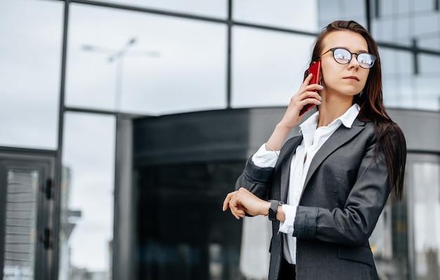 비즈니스 여성이 회의를 기다리는 근무일 동안 도시에서 시간을 확인하고 전화로 이야기합니다. 훈육과시기. 직원이 기업 회의에 참석합니다.
