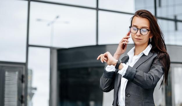 비즈니스 여성이 근무일 동안 도시에서 시간을 확인하고 전화로 이야기합니다.