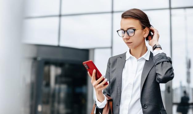 비즈니스 여성이 회의를 기다리는 근무일 동안 도시의 시간을 확인합니다. 훈육과시기. 직원이 기업 회의에 참석합니다.