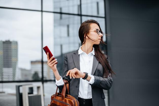 비즈니스 여성은 회의를 기다리는 근무일 동안 도시에서 시간을 확인합니다. 규율과 타이밍. 직원이 회사 회의에 참석합니다.