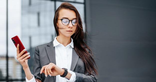ビジネスウーマンは、会議を待っている就業日の間に市内の時間をチェックします。規律とタイミング。従業員は企業の会議に向かいます。