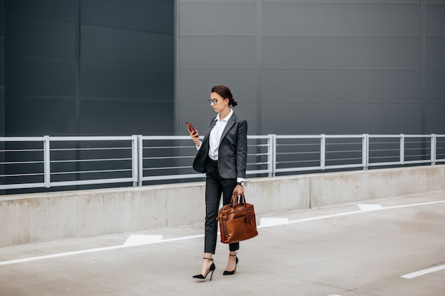 비즈니스 여성이 회의를 기다리는 근무일 동안 도시의 시간을 확인합니다.