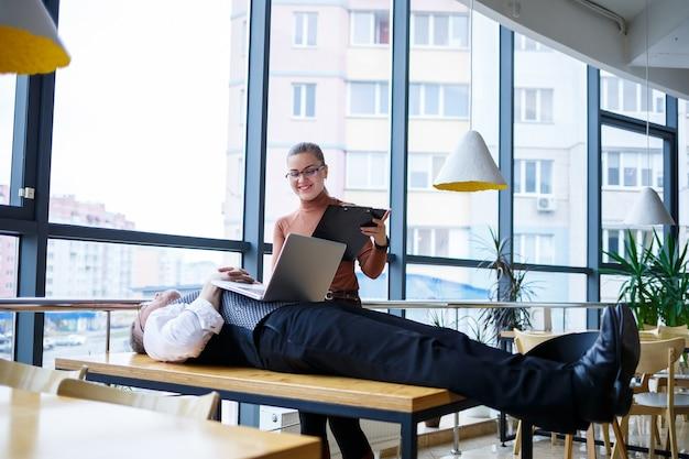 비즈니스 여자 여자가 서서 보고서를 읽고 있습니다. 피곤한 상사가 나무 탁자에 있는 탁자에 누워 있다. 사업가가 휴식을 취하고 부하 직원을 작업하고 있습니다.