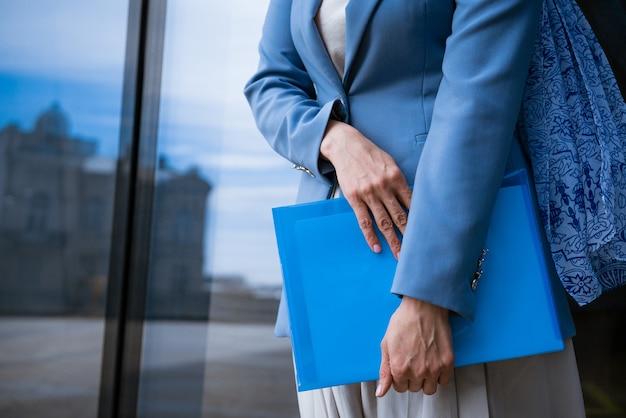 파란색 재킷에 비즈니스 여자는 유리 사무실 건물 앞에서 그녀의 손에 서류와 함께 폴더를 보유