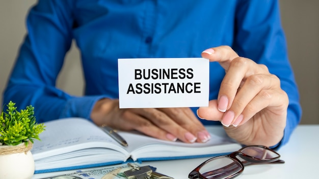 Деловая женщина в синей рубашке сидит за рабочим местом в офисе и держит листок бумаги с текстом: бизнес-помощь. бизнес-концепция.