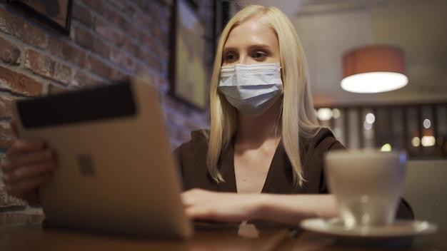의료용 마스크를 쓴 비즈니스 여성이 카페에서 태블릿을 사용하여 비디오 링크에 대해 이야기하고 있습니다. 작업 전화 통화, 원격 작업. 코로나 바이러스 감염병 유행. 클로즈업, 4k uhd.