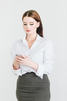 치마와 블라우스를 입은 비즈니스 여성이 스마트폰을 사용하여 의사소통과 미소를 짓습니다