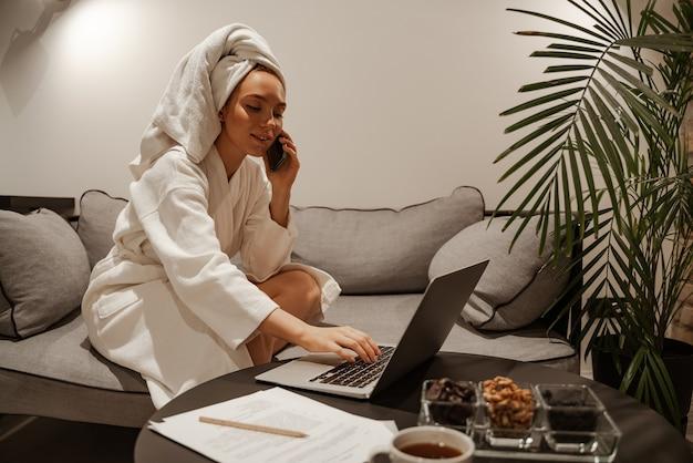 白いローブとタオルを着たビジネスウーマンは、ラップトップを使用してお茶やコーヒーを飲みます。彼女はソファに座っています。夜のリラクゼーション。