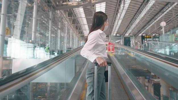 ビジネスウーマンは国際空港で保護マスクを着用し、covid-19パンデミックの下で旅行、安全な旅行、社会的距離のプロトコル、新しい通常の旅行の概念