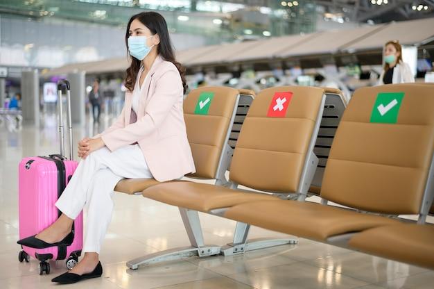 ビジネスウーマンが国際空港で防護マスクを着用し、covid-19パンデミックの下で旅行し、
