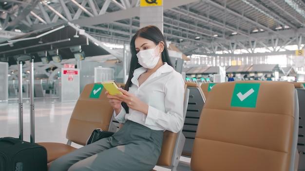 Деловая женщина в защитной маске в международном аэропорту путешествует в условиях пандемии covid-19