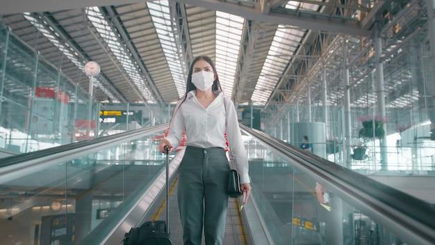 ビジネスウーマンが国際空港で保護マスクを着用し、covid-19パンデミックの下で旅行