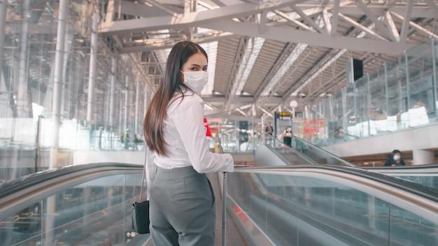 ビジネスウーマンが国際空港で保護マスクを着用し、covid-19パンデミックの下で旅行します
