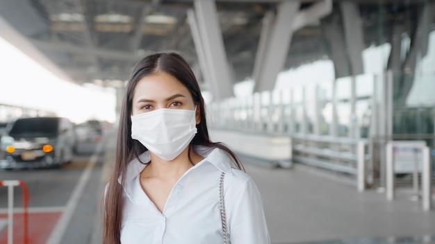 Деловая женщина в защитной маске в международном аэропорту