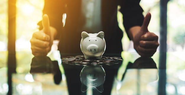 ビジネスの女性を作り、貯金箱とお金の概念を保存するためのテーブルの上のコインで手のサインを親指を表示